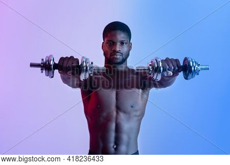 Portrait Of Motivated Black Weight Lifter With Naked Torso Working Out With Dumbbells In Neon Light