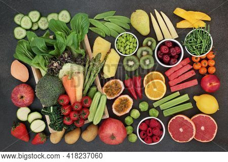 Clean eating high fibre food for a healthy digestive system with fruit and vegetables also high in antioxidants, anthocyanins, vitamins, minerals and protein. Health care concept. Flat lay on slate.