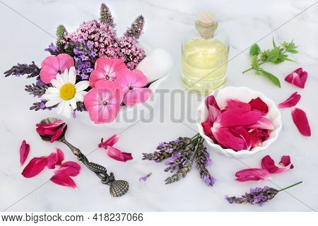 Natural herbal medicine preparation with flowers and  herbs in a mortar with pestle and  glass bottle of oil. Still life for naturopathic health care concept on marble background.