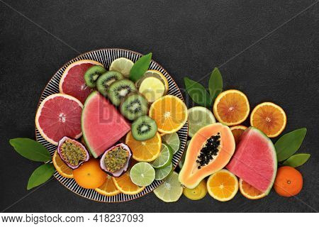 Winter sunshine healthy fruit concept high in antioxidants  anthocyanins for immune boost with papaya, melon, kiwi, passion fruit, oranges, lemons, limes  grapefruit also high in lycopene  vitamin c