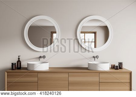 White And Wooden Stylish Bathroom Interior With Two Separate Sinks And Wooden Drawer With Bottles Of