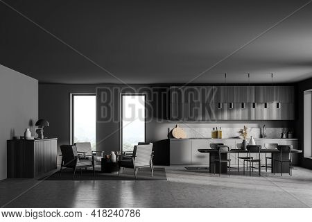 Stylish Interior Of Dark Grey Modern Kitchen Room With Dining Table And Chairs. Armchairs Livingroom
