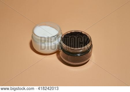 Coffee Scrub And Cosmetological Cream In Open Round Cans On Light Orange Background, Top View. Beaut