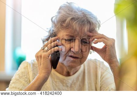 Shot of a tired senior woman using a mobile phone