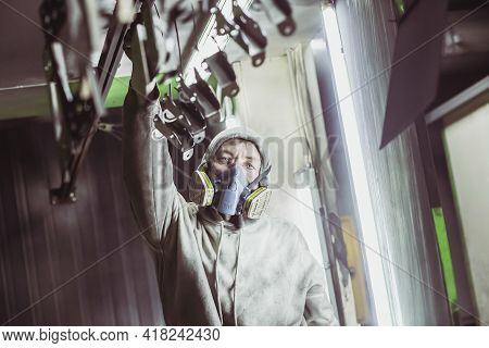 Bila Tserkva, Ukraine, March 2021: Worker Hangs Up Parts Before Painting In A Factory