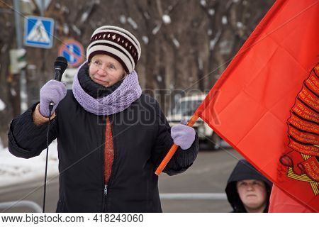 An Elderly Woman With A Microphone And A Red Communist Flag Speaks At An Opposition Rally. December