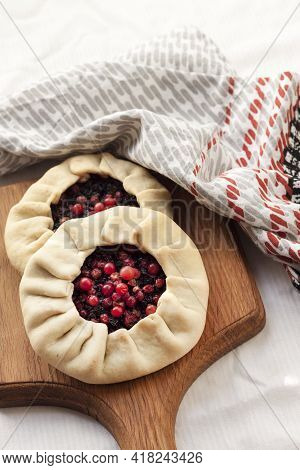Homemade Sweet Galette With Elderberries And Cowberries On A Wooden Board
