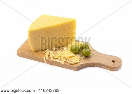 A Piece Of Hard Yellow Gouda Cheese And Grated Cheese With Olives On A Wooden Board. Close-up, Isola