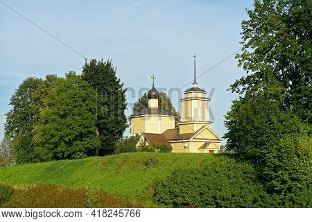 Wooden Church Of St. George The Victorious In Voronich Against The Blue Sky With Trees In The Backgr