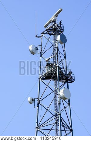 Tower With Coastal Surveillance Radar System And Various Communication Equipment On A Blue Sky Backg