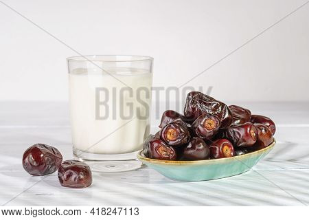 Delicious Dried Dates On A Blue Plate And Glass Of Milk On A White Wooden Table. Ready To Eat Natura