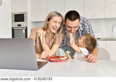 Happy Young Family Couple With Kid Son Having Fun Eating Toasts With Jam Using Laptop In Kitchen. Cu
