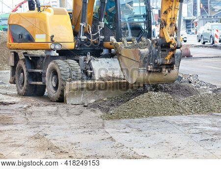 A Road Excavator Bucket Evenly Distributes Rubble To Create A Foundation On A Dirt Construction Site