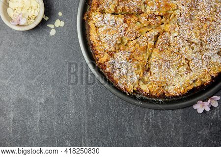 Almond Homemade Cake With Sliced Almonds Crust And Icing Powder Sugar On Dark Background. Top View.