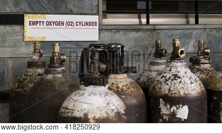 Signboard Notifying About Empty Oxygen Cylinders Behind A Stack Of Empty Cylinders In A Hospital War