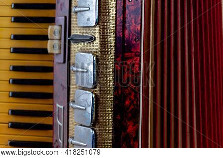Old Red 120 Bass Accordion Covered With Dust On Wooden Construction Background. Musical Instrument.