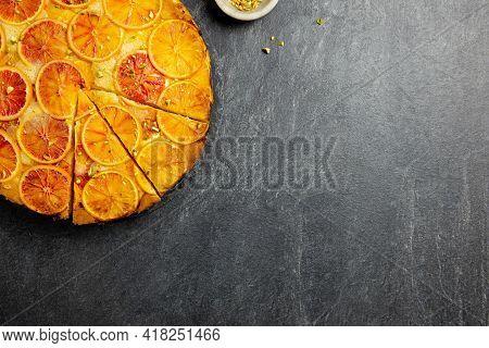 Upside Down Blood Orange And Polenta Cake With Pistachio Nut On Dark Stone Background. Homemade Cake
