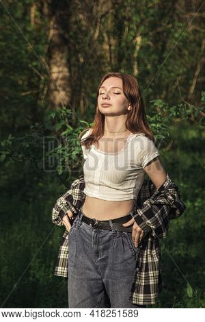 A Girl Stands Under The Rays Of The Sun In A Nature Photo. Enjoy The First Rays Of The Sun. Bask In