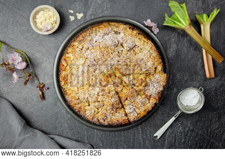 Homemade Cake With Rhubarb And Almond Flakes Crust On Dark Background. Top View.