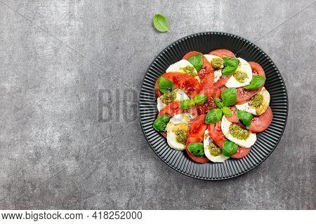 Traditional Italian Caprese Salad With Sliced Tomatoes, Mozzarella, Basil, Pesto Sauce And Spice On