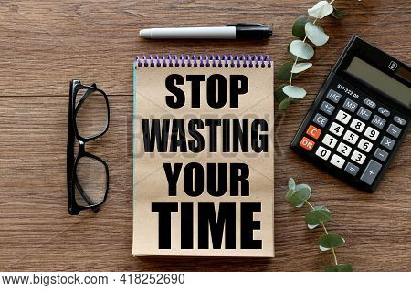 Stop Wasting Your Time. Lies On A Wooden Background, A Notebook With Craft Pages. Text On Notepad.