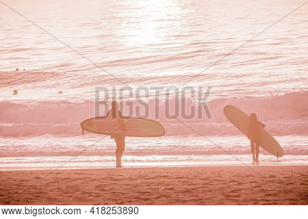 Pink Ocean Landscape In Sunset Time Background With Sandy Beach And Wavy Sea. Surfers On The Water L