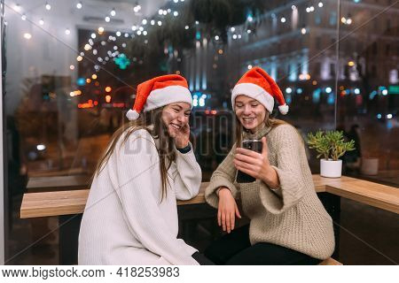 Two Young Girls Using Smartphone At The Cafe.