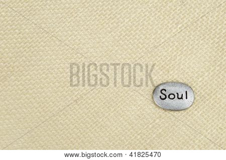 Silver stone with the word soul placed in lower right corner of tan burlap textured background