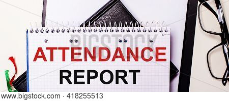 The Words Attendance Report Is Written In Red In A White Notebook Next To Black-framed Glasses.