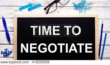 Time To Negotiate Written On A Black Note-board Next To Blue Paper Clips, Pencils And A Pen.