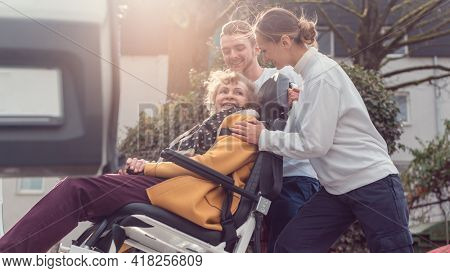 Two helpers picking up disabled senior woman for transport