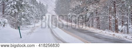 winter travel in Colorado Rocky Mountains - highway in Poudre Canyon in a heavy early spring snowstorm, panorama banner