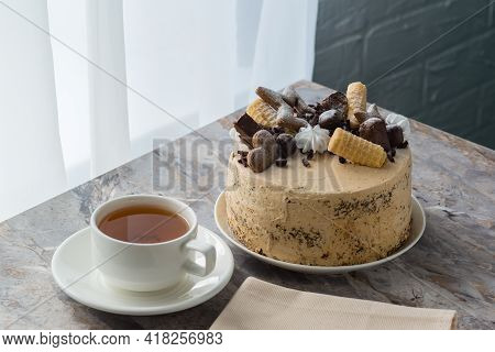 A Cup Of Tea On A Saucer And A Sponge Cake With Buttercream On The Marble Countertop Near The Window