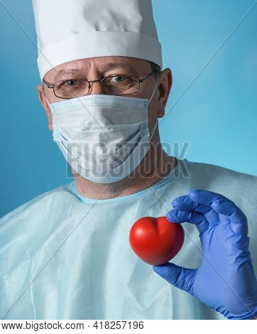 Portrait Of A Middle-aged Serious Experienced Cardiologist Surgeon In Medical Clothing: Cap, Gloves,
