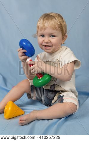 A Small Child Is A Cheerful Blue-eyed Blonde Sitting On A Blue Background And Playing With Toys. Sev