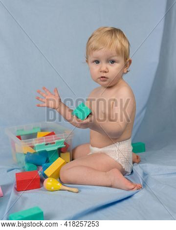 A Little Girl Of 1 Year In A White Diaper Sits On A Blue Background With A Multi-colored Constructor