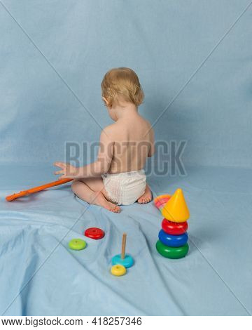 A Little Blonde Girl In A Diaper Sits On A Blue Background With Toys And Toys. Rear View. The Child