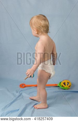 A Small Blond Boy Of 1 Year In A White Diaper Stands On A Blue Background. View From The Back