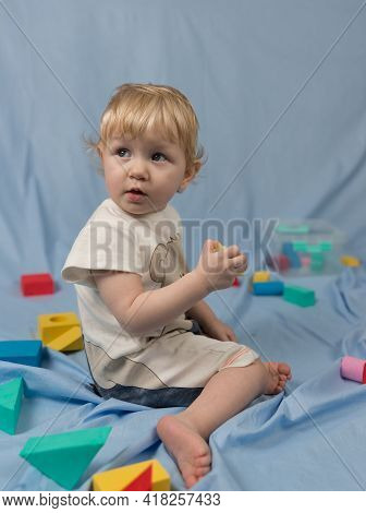 A Small Blonde Girl In A Short Jumpsuit Sits And Plays With Colorful Cubes With A Constructor