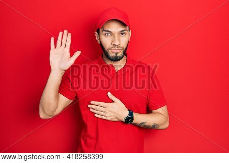 Hispanic man with beard wearing delivery uniform and cap swearing with hand on chest and open palm, making a loyalty promise oath