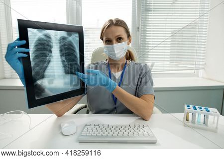 Portrait of female radiologist in mask and gloves sitting at desk with computer keyboard and test tube rack and explaining x-ray image to you