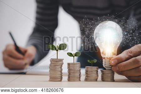Thinking And Creative With Coins And Light Bulb Concept,close Up Light Bulb And Working On The Desk,
