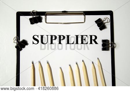 Suppliers Text Written On A White Notepad With Colored Pencils And A Yellow Background. Word