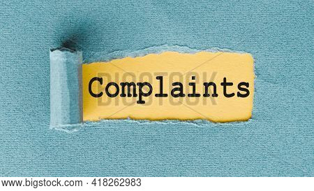 Complaints Word Written Under Torn Paper On Yellow