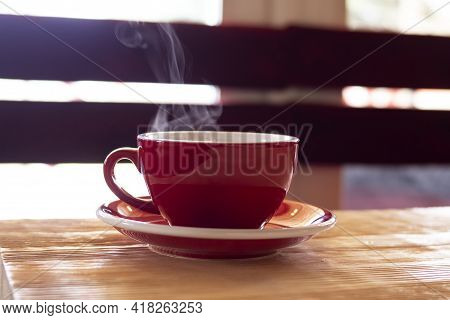 Red Cup With Steam On The Table Close Up