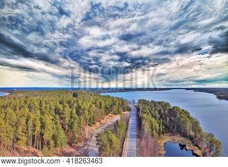 aerial view with road between lake and green pine forest
