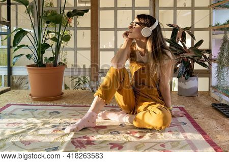 Satisfied Woman Wearing Headset Listen To Music Relaxed After Remote Work Day At Home. Cute Female G