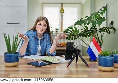 Female Student Sitting At Home Studying Online, Looking At Smartphone Webcam