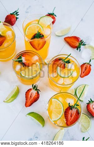 Fresh Orange Strawberry Mojito In Different Glasses With Ice Cubes And Slices Of Lime On The Table.