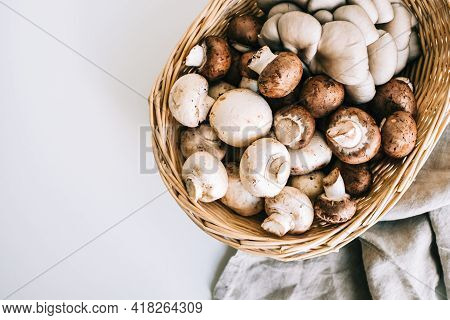 Fresh Mushrooms Champignons And Oyster Mushrooms In Basket With Linen Fabric Cloth On White Table, T